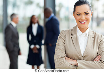attractive business executive with arms folded in office