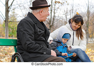 Three generations of a family at the park with an elderly...