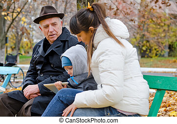 Family outing to the park with an elderly grandfather , his...