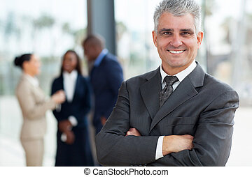 senior business executive with arms folded - smiling senior...