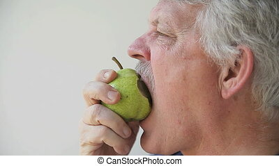 man eats pear - profile view of senior man eating a pear