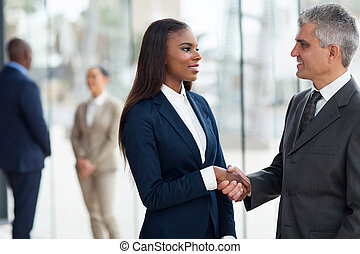 senior businessman handshaking with young businesswoman