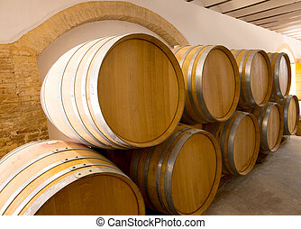 wine wooden oak barrels stacked in a row at winery - wine...