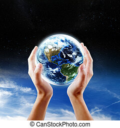 Saving Earth concept - Hands holding Earth with a sky and...