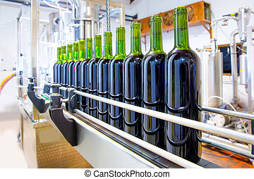red wine in bottling machine at winery - red wine in glass...