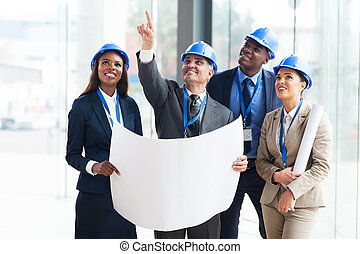 group of construction workers discussing project - group of...