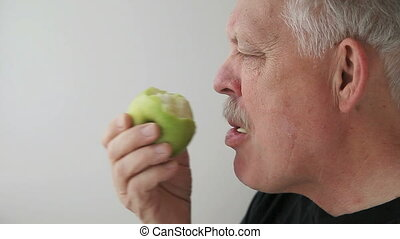 man eats green apple