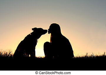 Girl Kissing Dog Silhouette - a silhouette of a woman with...