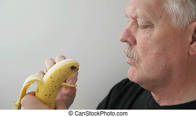senior man eats banana - profile view of older man eating...