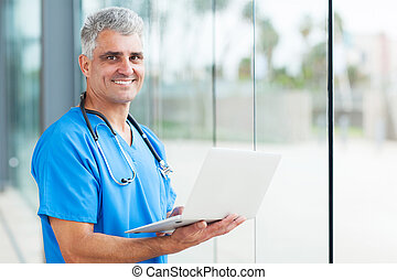 senior male nurse using laptop - handsome senior male nurse...