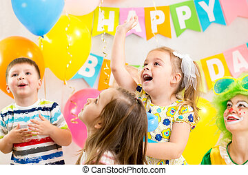 jolly kids group with clown celebrating  birthday party
