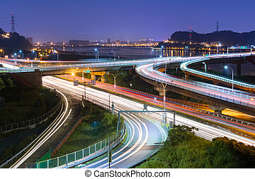 Night scene of cars light at highway and interchange in...