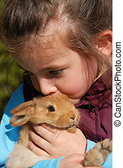 little girl and her bunny - little girl kissing her young...