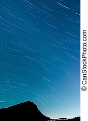 Star Trails with silhouette of mountain