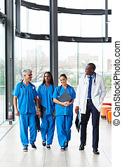 group of health care workers walking in hospital