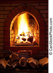 fire in fireplace - poker, firewood and flames of fire in...