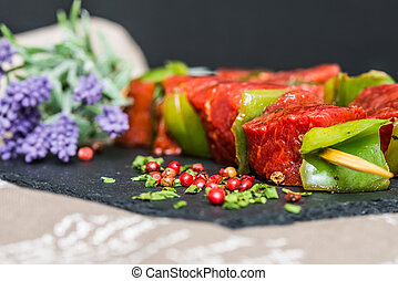 tasty beef steak kabobs with vegetables on a slate plate