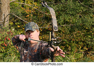 bow hunter with bow drawn - bow hunter pulling back on bow...