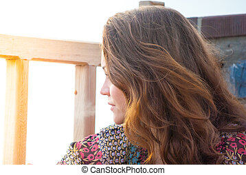 girl at sunset profile - girl with brown hair resting at...