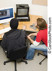 students editing video on computer in classroom
