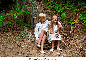 Boy and girl sitting on log in woods. - Portrait of cute...