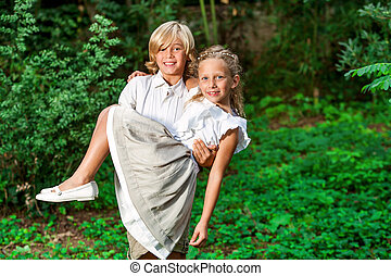 Cute boy carrying girl in arms.