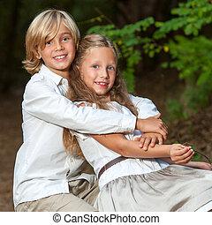 Cute boy hugging girlfriend in park.