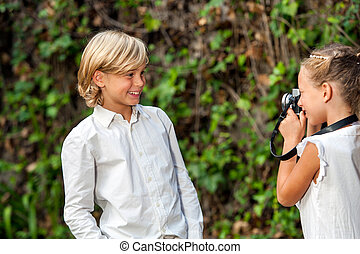 Girl taking pictute of boy outdoors - Cute young couple...