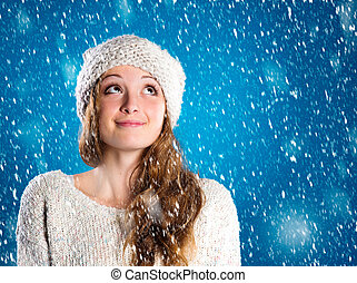 Beautiful woman in warm sweater with snowflakes around her,...