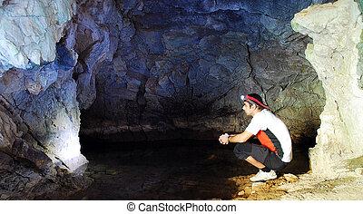 cave exploring - man exploring a cave