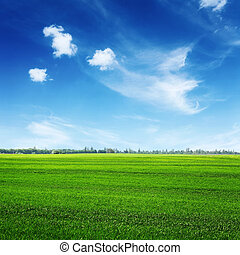 green field and clouds on blue sky - green spring field and...