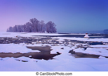 winter river with cracked ice and light after sunset in haze