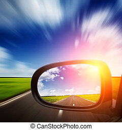 car mirror with blue sky above road and blurred motion