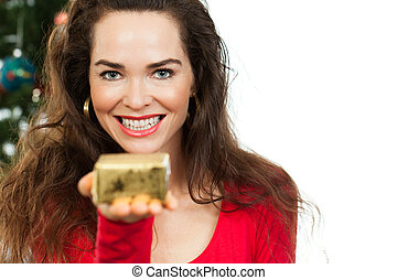 Beautiful woman holding out Christmas gift