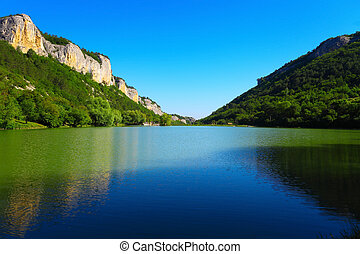 Mountain lake between the rocks and green trees