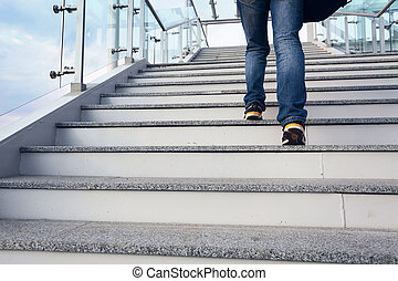 man on office stairs and blue sky, legs closeup