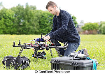 Engineer Preparing Surveillance Drone in Park - Young...