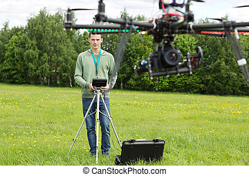 Technician Flying UAV Helicopter - Young technician flying...