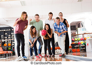 Woman Bowling While Friends Motivating in Club - Confident...