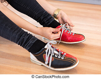 Woman Tying Shoe Lace in Club - Low section of young woman...