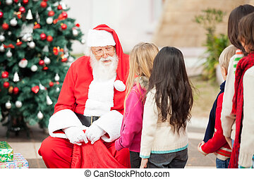 Santa Claus Looking At Children Standing In A Queue - Santa...