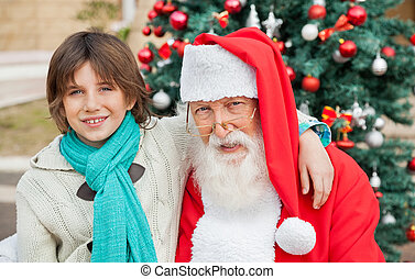 Boy With Arm Around Santa Claus Outdoors - Portrait of boy...