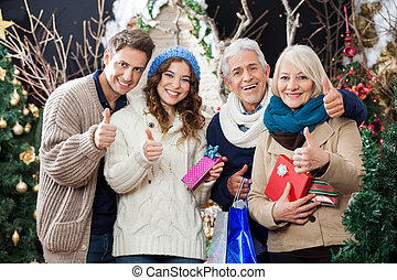 Happy Family Gesturing Thumbs Up In Christmas Store -...