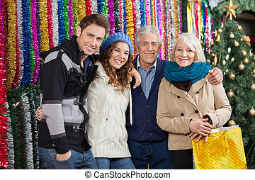 Family Standing Against Tinsels At Christmas Store -...