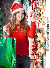 Woman With Shopping Bag Buying Christmas Ornaments -...