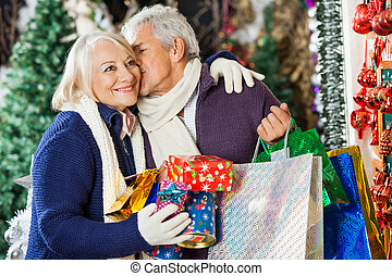 Man With Shopping Bags Kissing Woman At Store - Senior man...
