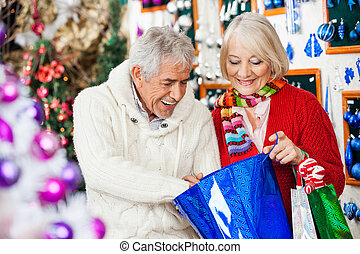 Happy Couple Looking Into Shopping Bag - Happy senior couple...