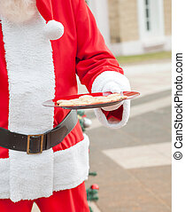 Santa Claus Holding Plate With Cookies - Midsection of Santa...