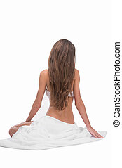 Naked beauty. Rear view of young woman in lingerie sitting...