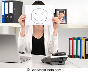 Making a smiley face. Businesswoman sitting at her working face and holding poster with smile in front of her face
